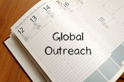 Global outreach write on notebook Royalty Free Stock Photography