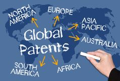 Global Patents. Female hand writing text on blue world map background Royalty Free Stock Photo