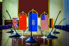 Global security. National flag of different countries in the empty conference room, concept of global security. Focus on the UN, Chinese and United Stats flag Stock Image