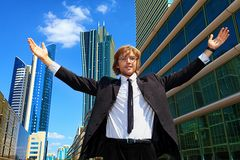 Global success. Young business man standing in the big city and purposefully looking away Stock Image