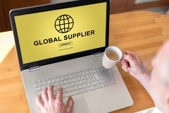 Global supplier concept on a laptop. Man using a laptop with global supplier concept on the screen Stock Photo