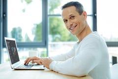 Cheerful intelligent man working. Global trade. Cheerful intelligent positive man using a laptop and working while studying global trade Royalty Free Stock Image