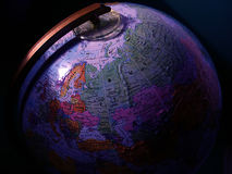 Global View. A globe with light cast on its surface, dark shadows Stock Images