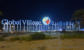 The Global Village sign at night, Dubai Stock Images