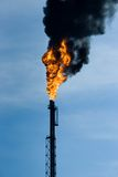 Global warming. Refinery funnel burning with huge flame and throwing clouds of dark smoke Stock Photos