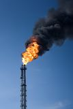 Global warming. Refinery funnel burning with huge flame and throwing clouds of dark smoke Royalty Free Stock Photography