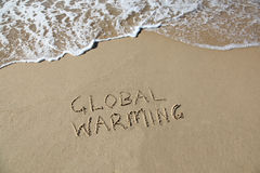 Global warming. Written in the sand at beach with rising wave Royalty Free Stock Photos
