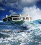 Global warming. A building floating on a large wave or tsunami. Concept for global warming royalty free stock photos