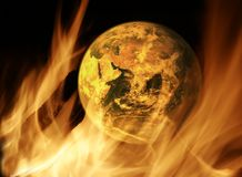 Global warming. Concept: global warming with the earth on flaming background Stock Photos