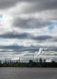 Global Warming. Industrial landscape including river in foreground and factory smokestacks on horizon against an ominous sky Royalty Free Stock Photos