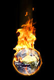 Global warming. An illustration of our world burning in flames and representing by a metaphor the consequences of the global warming. Isolated on a black royalty free stock images