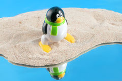 Global warming. Penguin stands on a sandy island surrounded by water instead of an iceberg, concept of global warming Royalty Free Stock Photo