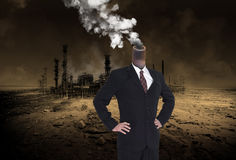 Global Warming, Business Greed, Apocalypse. A businessman stands in a desolate desert and has a polluting smokestack for a head. In the background a big urban royalty free stock photos