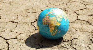 Global warming concept. Global warming - miniature Earth on a dry land texture Royalty Free Stock Images