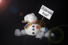 Global warming. Concept made with snowman, ice cubes, protest sign. Till global warming do us part! The statement written on the protest sign, carried by a stock photo