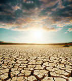 Global warming. Dramatic sky over cracked earth Royalty Free Stock Image