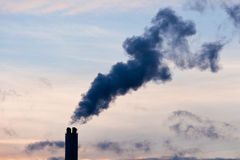 Global warming industrial pollution smoke concept. Smokestack chimney belching black smoke and pollutants in blue evening sky contributing to global warming and Stock Photos