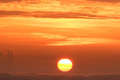 Global warming. Setting sun. A simple beautiful cloudscape with the sun setting low above the clouds Stock Photo