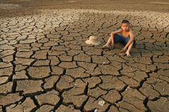 Children and climate change. Children farmer sit on cracked earth. metaphoric for climate change and global warming Royalty Free Stock Images
