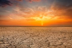 Cracked earth soil sunset landscape. Global worming concept - cracked scorched earth soil drought desert landscape dramatic sunset Royalty Free Stock Photo