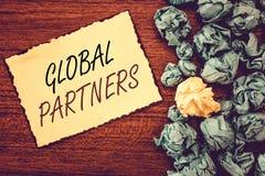 Globala partners för ordhandstiltext Affärsidé för två eller mer firmor från olika länder arbeta som ett lag arkivbild