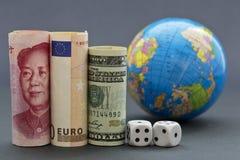 Globala risker reflekterade i tre valutor, tärning och jordklot Royaltyfria Bilder