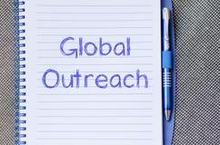 Globaler Outreach schreiben auf Notizbuch stockfotos