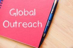 Globaler Outreach schreiben auf Notizbuch lizenzfreie stockbilder