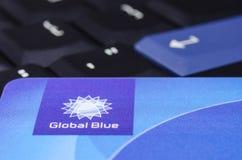 Globales blaues Nahaufnahmelogo auf Plastikkarte gegen schwarzes ThinkPad Stockbilder