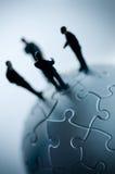 Globales Team auf einem Puzzlespiel Stockbild