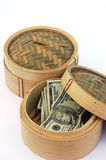 Globalisation. USA or American currency - cash - in a chinese dim sum steaming basket Royalty Free Stock Photos