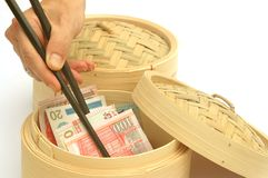 Globalisation Hong Kong China 2. Hong Kong money in a dim sum steaming basket being removed with chopsticks - metaphor for trade, globalisation, etc stock images