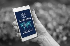 Globalization concept on a smartphone. Female hand holding a smartphone with globalization concept stock photos
