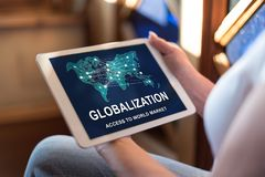 Globalization concept on a tablet. Woman holding a tablet showing globalization concept royalty free stock image