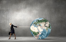 Globalization concept. Young businesswoman holding Earth planet on lead. Elements of this image are furnished by NASA Royalty Free Stock Image