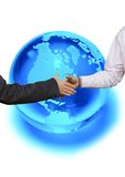 Globally Binding. Business handshake in front of a blue globe royalty free stock photo