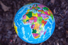 Globalna piłki zabawka na glebowym tle, środowiska pojęcie Obrazy Royalty Free