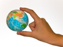 Globe. A child's hand holding up a small colored world globe on an isolated background Royalty Free Stock Images