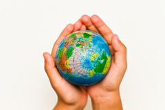 Globe. A child's hand holding up a small colored world globe on an isolated background royalty free stock photography
