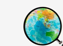 Globe. A magnifying glass view of a small colored globe isolated on a white background royalty free stock photos