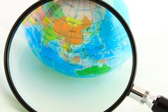 Globe. A magnifying glass view of a small colored globe isolated on a white background Stock Image