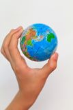 Globe. A child's hand holding up a small colored world globe on an isolated background stock photography