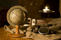 Globe. An old globe in a scene with a pair of flying goggles and a candle Royalty Free Stock Photos