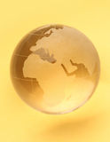 Globe. Isolated on yellow background with reflection Stock Photos