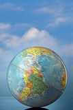 Globe. Against cloudy sky Royalty Free Stock Photo