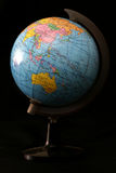 Globe. A globe lit from the left with a dark background Royalty Free Stock Photos