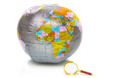 Globe with Africa and a magnifying glass Stock Images