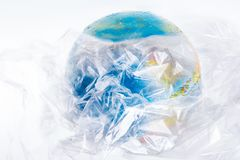 The globe is all in plastic, our irresponsible, excessive consumption of plastic. The globe is all in plastic, social advertising, world environment day concept Royalty Free Stock Photos