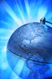 Globe America. A metallic globe with the focus on America with rays and beams of blue light Royalty Free Stock Images