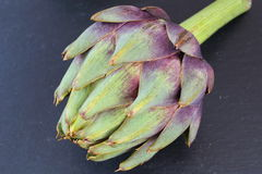 Globe artichoke on a slate plate Royalty Free Stock Images